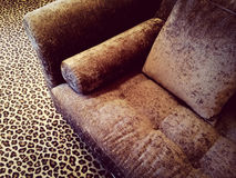 Velvet sofa on leopard carpet Stock Photo