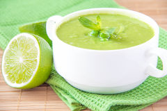 Velvety cream soup from a gentle green peas. With mint and lime on green towel Royalty Free Stock Photos