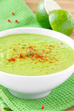 Velvety cream soup from a gentle green peas with paprika. Velvety cream soup from a gentle green peas with mint and lime in white bowl on green towel Stock Images