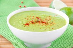 Velvety cream soup from a gentle green peas with paprika. Velvety cream soup from a gentle green peas with mint and lime in white bowl on green towel Stock Image