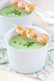 Velvety green cream soup of broccoli, peas, spinach, fry shrimp Royalty Free Stock Photos