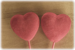 Velvety Hearts on Wood - Retro. Two coral pink soft velvety hearts on sticks against a wood background.  Cross processed in retro hues and given a soft white Royalty Free Stock Photos