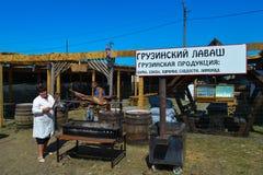 Woman preparing whole lamb on BBQ at national Ukrainian annual market `Sorochinska. Velyki Sorochintsi, UKRAINE - AUGUST 25, 2017: Woman preparing whole lamb on Royalty Free Stock Images