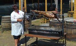 Woman roasting whole sheep on BBQ at national Ukrainian annual market `Sorochinska. Velyki Sorochintsi, UKRAINE - AUGUST 25, 2017: Woman roasting whole sheep on Royalty Free Stock Photos