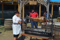 Woman roasting whole sheep on BBQ at national Ukrainian annual market `Sorochinska. Velyki Sorochintsi, UKRAINE - AUGUST 25, 2017: Woman roasting whole sheep on Royalty Free Stock Photo