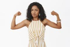 Vem säger den svaga flickan Stående av allvarlig-att se den starka och kraftiga afrikansk amerikankvinnan med den lockiga frisyre royaltyfri bild
