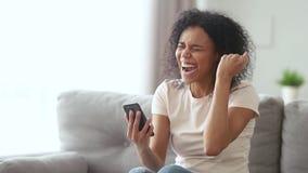 Vencedor afro-americano novo feliz da mulher que grita olhando o smartphone filme
