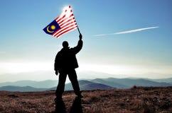 Vencedor bem sucedido do homem da silhueta que acena o fla de Malásia fotografia de stock royalty free