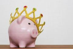 Vencedor ou rei financeiro do conceito das economias do dinheiro, mealheiro cor-de-rosa feliz de sorriso que veste uma coroa dour imagem de stock royalty free