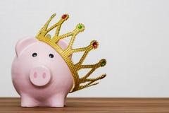 Vencedor ou rei financeiro do conceito das economias do dinheiro, mealheiro cor-de-rosa feliz de sorriso que veste uma coroa dour imagens de stock royalty free