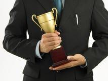 Vencedor que prende um throphy Imagem de Stock