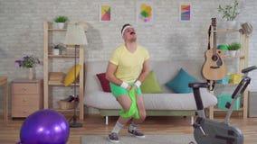 Vencido engraçado do homem que faz a aptidão em casa com a ajuda das faixas elásticas mo lento vídeos de arquivo