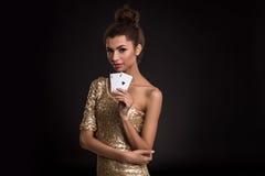 Vencimento da mulher - a jovem mulher em um vestido elegante do ouro que guarda dois áss, um pôquer dos áss carda a combinação Imagem de Stock Royalty Free