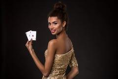 Vencimento da mulher - a jovem mulher em um vestido elegante do ouro que guarda dois áss, um pôquer dos áss carda a combinação Fotografia de Stock Royalty Free