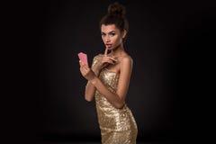 Vencimento da mulher - a jovem mulher em um vestido elegante do ouro que guarda dois cartões, um pôquer dos áss carda a combinaçã Imagem de Stock