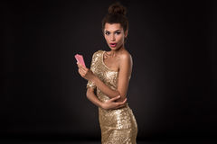 Vencimento da mulher - a jovem mulher em um vestido elegante do ouro que guarda dois cartões, um pôquer dos áss carda a combinaçã Imagens de Stock