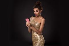 Vencimento da mulher - a jovem mulher em um vestido elegante do ouro que guarda dois cartões, um pôquer dos áss carda a combinaçã Imagem de Stock Royalty Free