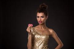 Vencimento da mulher - a jovem mulher em um vestido elegante do ouro que guarda duas microplaquetas vermelhas, um pôquer dos áss  Imagem de Stock Royalty Free