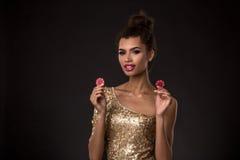 Vencimento da mulher - a jovem mulher em um vestido elegante do ouro que guarda duas microplaquetas vermelhas, um pôquer dos áss  Fotografia de Stock