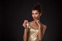 Vencimento da mulher - a jovem mulher em um vestido elegante do ouro que guarda duas microplaquetas vermelhas, um pôquer dos áss  Imagens de Stock