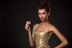Vencimento da mulher - a jovem mulher em um vestido elegante do ouro que guarda duas microplaquetas vermelhas, um pôquer dos áss  Fotos de Stock Royalty Free