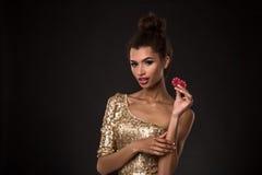 Vencimento da mulher - a jovem mulher em um vestido elegante do ouro que guarda duas microplaquetas vermelhas, um pôquer dos áss  Imagem de Stock