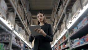 Venda, compra, consumição e conceito dos povos - próximo acima da jovem mulher com o computador do PC da tabuleta no mercado, sup Fotos de Stock