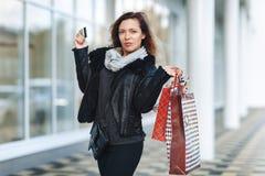 Venda, compra, turismo e conceito feliz dos povos - mulher bonita com sacos de compras e cartão de crédito nas mãos em uma rua Imagens de Stock Royalty Free