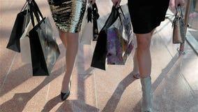 Venda, consumição e conceito dos povos - jovens mulheres felizes com sacos de compras que andam ao longo do shopping, estudante d video estoque