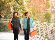 Venda, consumição e conceito dos povos - jovens mulheres felizes que olham em sacos de compras na loja na cidade imagem de stock