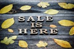 A venda da inscrição está aqui, o fundo de madeira, quadro das folhas amarelas foto de stock royalty free