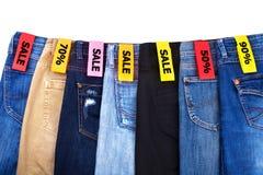 Venda da loja da roupa, cal?as de brim das cores diferentes azuis, verde, preto fundo branco no fim isolado acima foto de stock royalty free