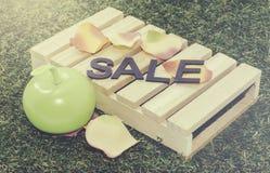 Venda da palavra do conceito da imagem na pálete, na luz da maçã com pétala artificial e na grama Imagem de Stock