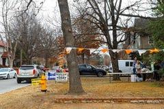 A venda da propriedade da vizinhança em casa para a venda no inverno com muitos carros estacionou nas ruas e nos povos que espera fotos de stock