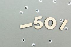 -50% venda de figuras de madeira em um fundo de papel cinzento foto de stock royalty free