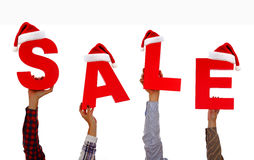 Venda do Natal Mãos guardando cartões com a venda da palavra com parte dianteira do chapéu de Santa acima Fotografia de Stock Royalty Free