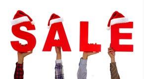 Venda do Natal Mãos guardando cartões com a venda da palavra com parte dianteira do chapéu de Santa acima Imagens de Stock Royalty Free