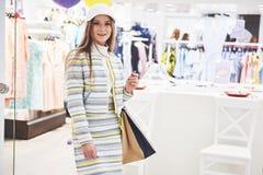 Venda, forma, consumição e conceito dos povos - jovem mulher feliz com os sacos de compras que escolhem a roupa na alameda ou imagem de stock royalty free