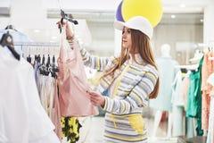 Venda, forma, consumição e conceito dos povos - jovem mulher feliz com os sacos de compras que escolhem a roupa na alameda ou fotos de stock