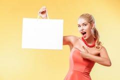 Venda Mulher de sorriso nova que mostra o saco de compras no feriado preto de sexta-feira Menina no fundo amarelo com espaço da c imagens de stock royalty free