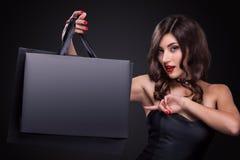 Venda Mulher de sorriso nova que mostra o saco de compras no feriado preto de sexta-feira Menina no fundo escuro com espaço da có imagem de stock