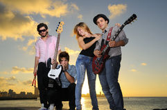 Venda musical joven fresca que presenta en la puesta del sol Fotografía de archivo