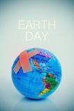 Vendajes adhesivos en un globo terrestre y el Día de la Tierra del texto Fotos de archivo libres de regalías