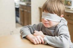 Vendaron los ojos de al niño en casa Fotografía de archivo libre de regalías