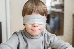 Vendaron los ojos de al niño en casa Fotos de archivo