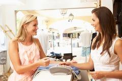 Vendas assistentes na verificação geral da loja de roupa Imagem de Stock