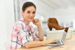 Vendas de observação da sapata da jovem mulher no Internet Foto de Stock