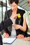 Vendas do carro - negociante que entrega a chave do automóvel da mulher Imagens de Stock Royalty Free