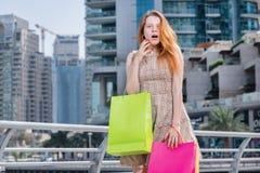 Vendas e surpresa Moça que guarda sacos de compras e olhares fixos Imagens de Stock