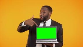 Vendedor afro-americano de sorriso que mostra o portátil prekeyed, lugar para a propaganda filme
